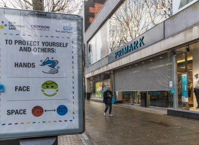 A man wearing a face mask walks past a closed Primark shop in Croydon in England yesterday.