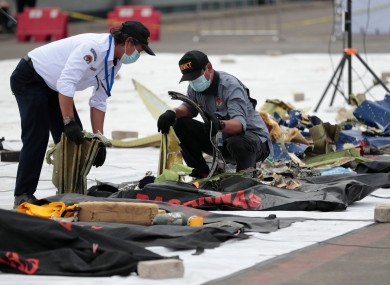 Investigators of the National Transportation Safety Committee inspect parts of the aircraft's debris recovered from the Java Sea.