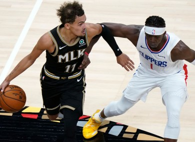 Atlanta Hawks guard Trae Young drives against Los Angeles Clippers guard Reggie Jackson.