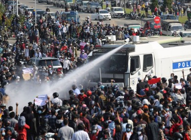 A police truck sprays water to a crowd of protesters in Naypyitaw