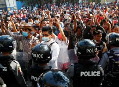 Residents and protesters face riot police in the city of Mandalay