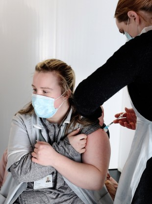 A home care assistant receives a vaccine in the Helix in DCU.