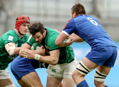 Ireland's Robbie Henshaw is tackled by Anthony Jelonch of France.