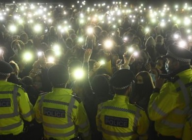 People shine phone camera lights at the protest in Clapham