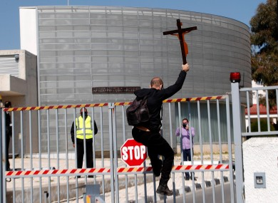 A protestor holding a cross climbs a gate outside Cyprus's national broadcasting building
