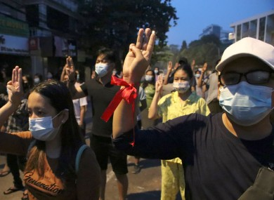 Anti-coup protesters flash three-fingered gesture, a symbol of resistance, during a rally outside their homes in downtown Yangon, Myanmar