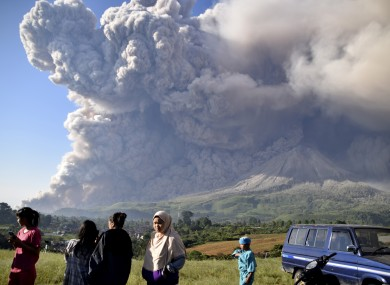 People watch as Mount Sinabung spews volcanic material during an eruption in Karo, North Sumatra
