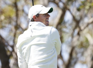 McIlroy watches anxiously on from the tee.