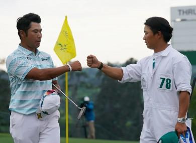 Matsuyama is congratulated by caddie Shota Hayafuji after a third-round 65.