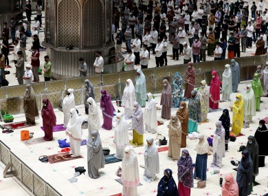 Indonesian Muslims pray spaced apart as they practice social distancing to curb the spread of the new coronavirus during an evening prayer called