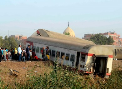 People gather at the site where a passenger train derailed in Egypt
