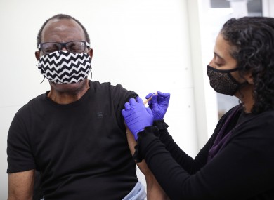 Pharmacist Asha Fowells vaccinates Paul Jinadu, 79.