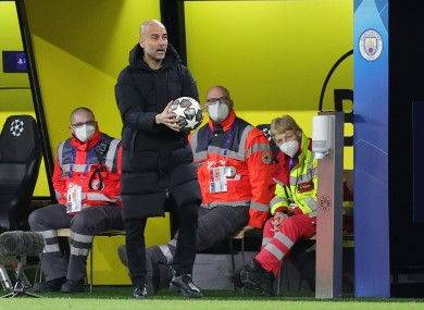 Man City manager Pep Guardiola holding a Champions League ball during his side's victory in Dortmund.