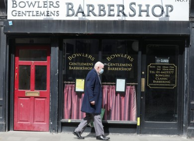 A man walks by a Dublin Barber shop as the nation waits to hear about reopening.