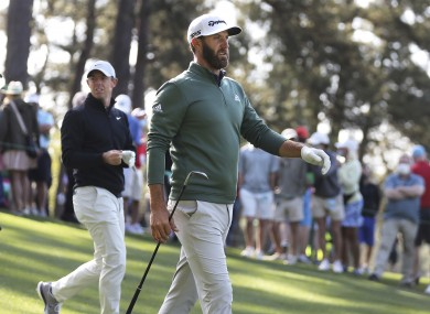 Defending Masters champion Dustin Johnson and Rory McIlroy walk the fourth fairway after teeing off during their practice round yesterday.