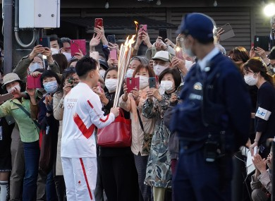 People taking pictures as a torch bearer shows the torch before a relay run in Tokyo today.
