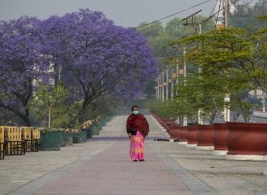 A Nepalese woman walks on a deserted street during the first day of lockdown in Kathmandu, Nepal
