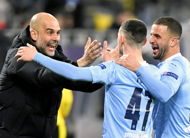 Pep Guardiola embraces Phil Foden and Kyle Walker.