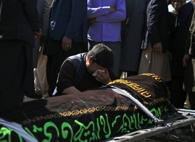 An Afghan man cries over the victim of deadly bombings at a cemetery west of Kabul on Sunday.