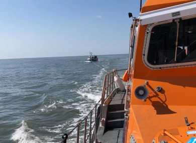 The RNLI lifeboat towing the fishing vessel
