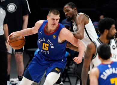 Nikola Jokic, left, drives on Kevin Durant: Durant's Nets were 125-119 winners.