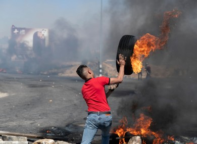 A Palestinian protester rolls a burning tyre towards Israeli army soldiers during clashes at the northern entrance of the West Bank city of Ramallah