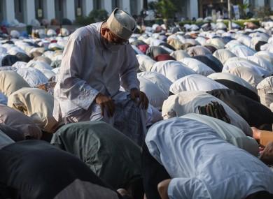 People wearing face masks perform Eid al-Fitr prayers at Al-Azhar Mosque in Jakarta.