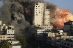 Smoke and flames rise from a tower building destroyed by Israeli air strikes in Gaza