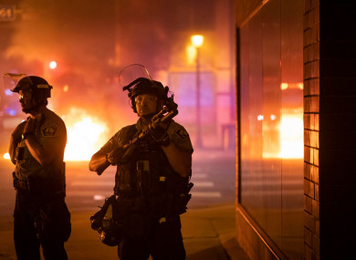 Police stand guard after protesters start fires after a vigil was held for Winston Boogie Smith Jr.