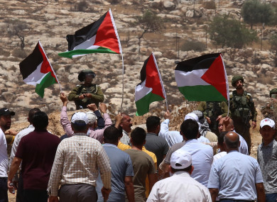 Protesters hold Palestinian flags in front of Israeli soldiers during a protest against the expansion of Jewish settlements in the village of Beit Dajan, east of the West Bank city of Nablus
