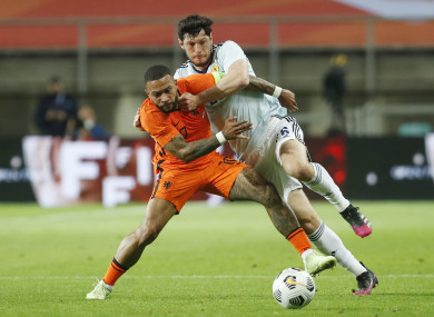 Netherlands' Memphis Depay challenges for the ball with Scotland's Scott McKenna.