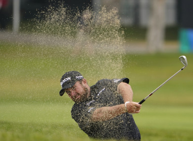 Shane Lowry hits from a bunker on the first fairway.