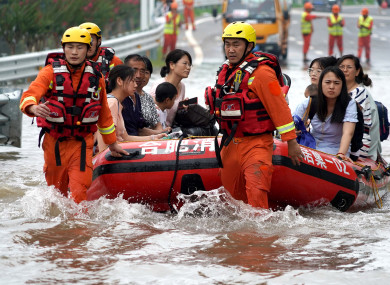 Rescuers help evacuate stranded people at the entry to an expressway in flood-hit Zhengzhou.