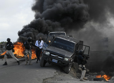 Police abandon their vehicle during a demonstration that turned violent in which protesters demanded justice for the assassinated President Jovenel Moise