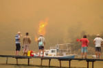 Onlookers watching a wildfire burn near the sea.