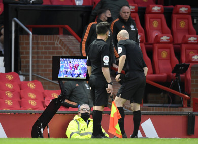 Referee Anthony Taylor consults with the VAR TV monitor at Old Trafford.