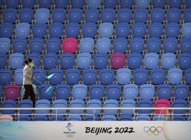A maintenance worker walks through an empty section of spectator stands near a logo for the Beijing 2022 Winter Olympics.